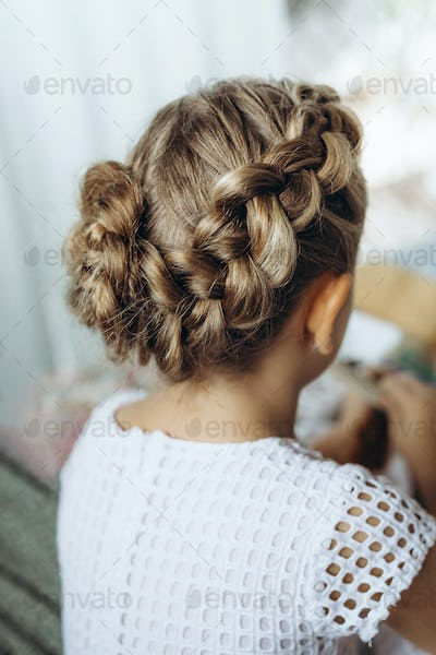 Festive hairstyle from braid on a child girl with long hair, back view