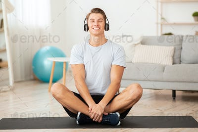 Music for training, yoga and relax. Happy young sportsman with closed eyes sits in lotus pose on mat
