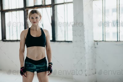 Muscular, strong and beautiful body. Smiling middle aged woman in sportswear with smart watch and