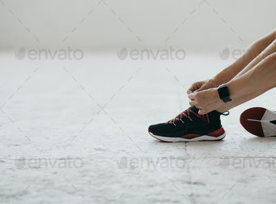 Woman with fitness tracker tying shoelaces on fashion sneakers, sitting on floor in gym or living