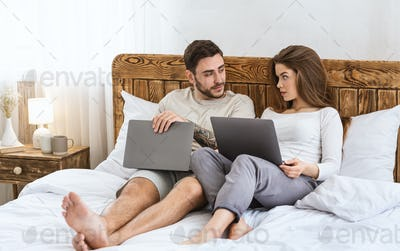 Modern evening leisure. Guy and girl lie on bed with laptops and talking