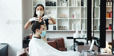 Hairdresser and male client wearing protective masks at salon