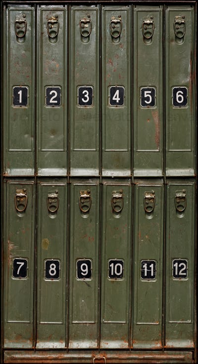 Old green metal cabinet with vertical storage compartments