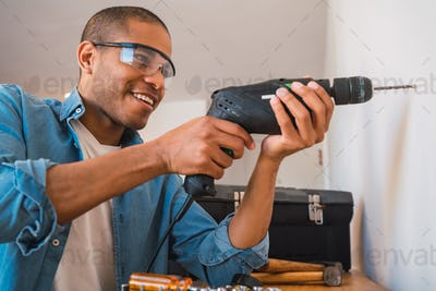 Young man with a electric drill and making hole in wall.