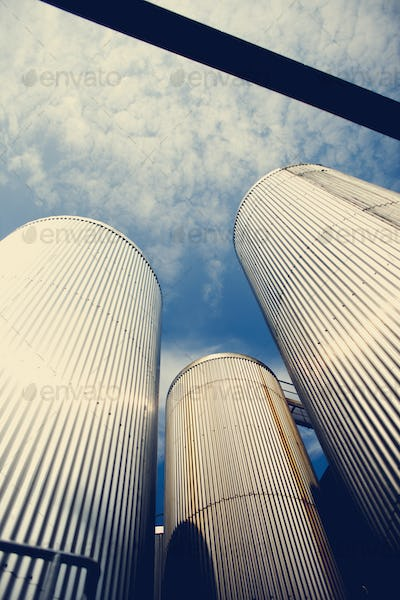 Low angle view of grain silos against blue sky