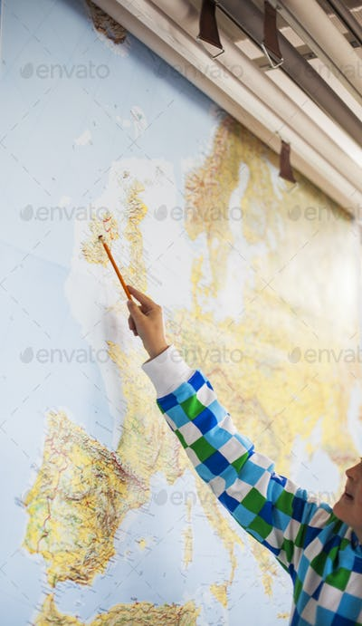 Cropped image of student pointing at map with pencil in classroom