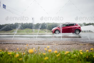 Water spraying on red car on road