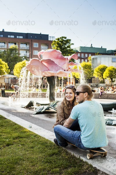 Happy woman sitting with man on skateboard at park in city