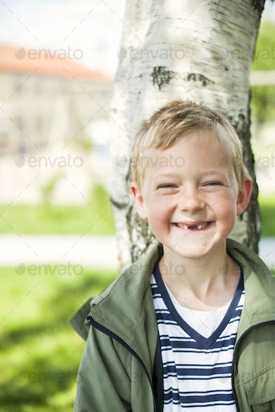 Portrait of happy schoolboy leaning on tree trunk at yard