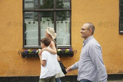 Side view of family walking against orange building in town