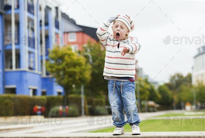Cute boy yawning while standing in city