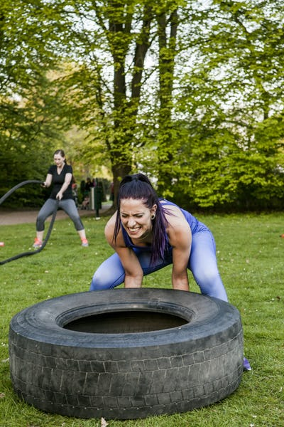 Determined women doing crossfit exercises at park