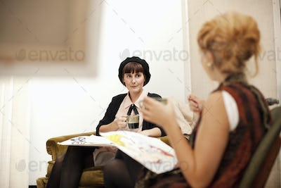Young female painters discussing paintings while drinking coffee at studio