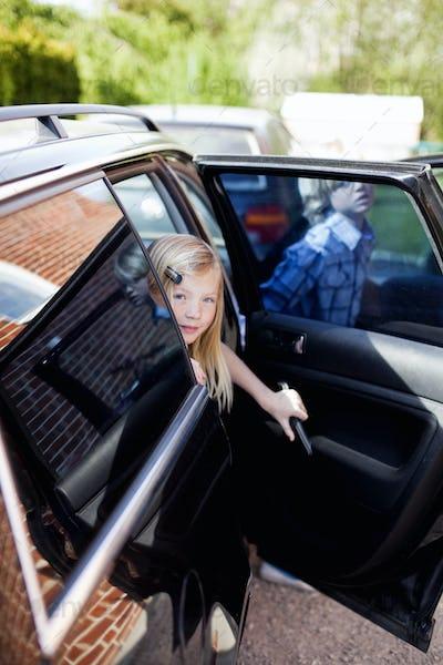 Girl sitting in car looking through open door