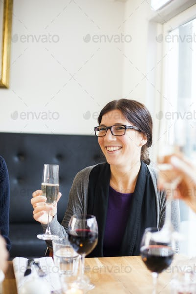 Happy woman looking away while holding champagne flute at restaurant table