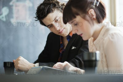 Business man and woman sitting at cafe during meeting