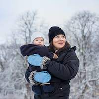 Mother carrying toddler while standing at park during winter