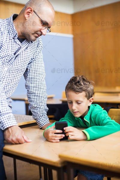 Teacher looking at schoolboy using smart phone in classroom