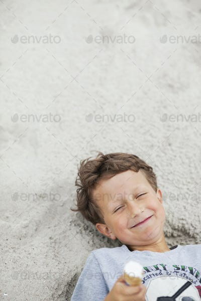 High angle view of happy boy lying with ice cream on sand at beach