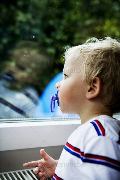 Close-up of boy sucking pacifier while looking through window