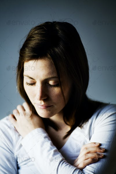 Close-up of woman with neckache against wall