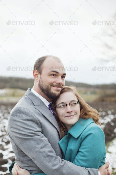 Smiling couple embracing while looking away against sky