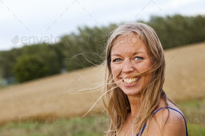 Portrait of cheerful woman looking away while standing on field