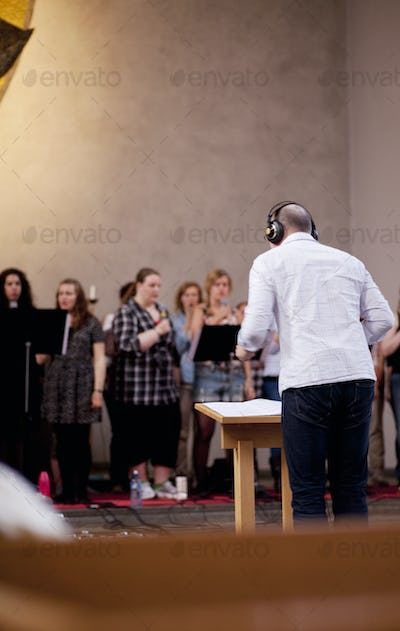Rear view of musical conductor with choir group singing in background at church