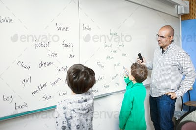 Teacher looking at schoolboy writing spellings on whiteboard in classroom