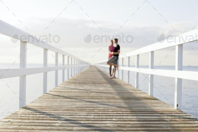 Distant image of romantic young couple kissing on pier