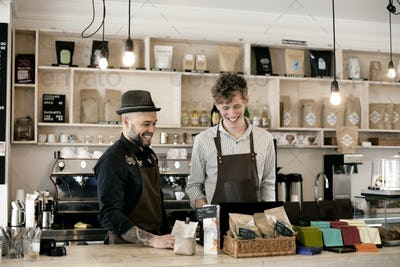 Smiling male baristas working at counter in coffee shop