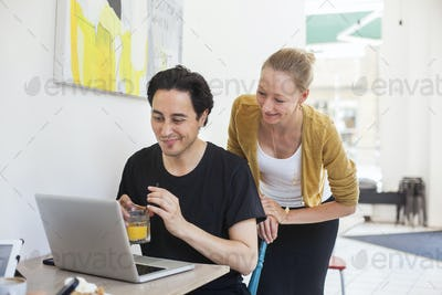 Happy man and woman using laptop at coffee shop
