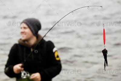 Man looking away while holding fishing rod in lake
