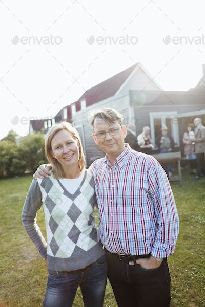 Portrait of couple in back yard against house