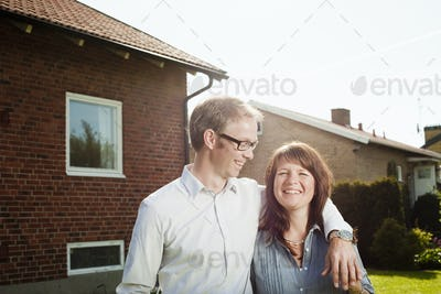 Happy couple standing with arm around in back yard against house