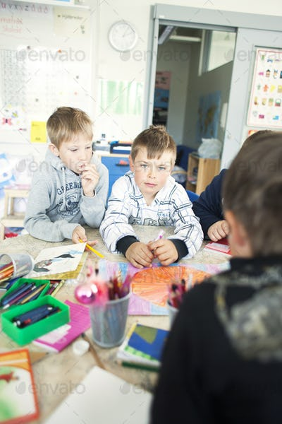 Portrait of schoolboy drawing with classmates at desk in classroom