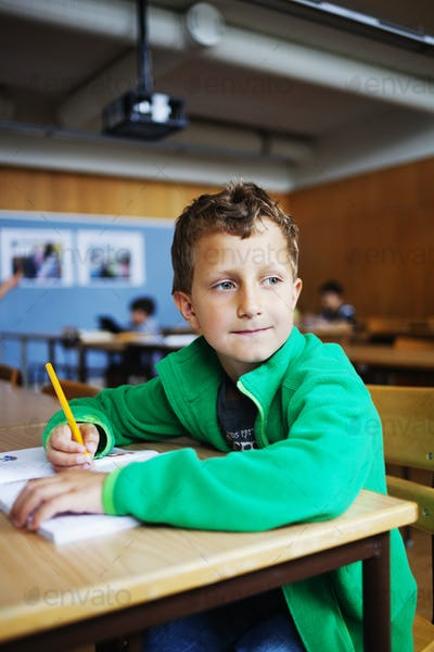 Boy sitting at desk with book and pencil while looking away in classroom