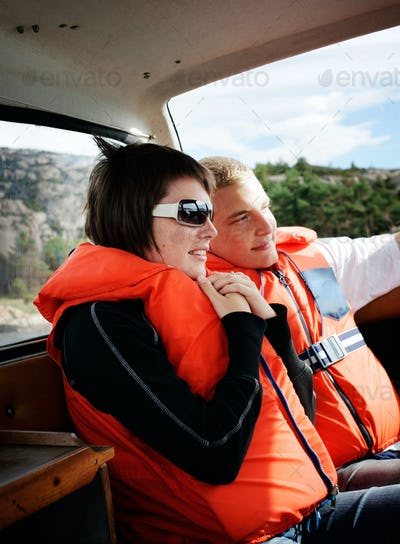 Smiling couple wearing life jackets while traveling in boat