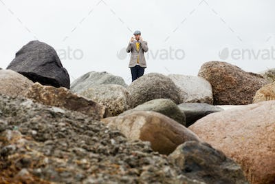 Man smoking pipe while talking on mobile phone amidst rocks against clear sky
