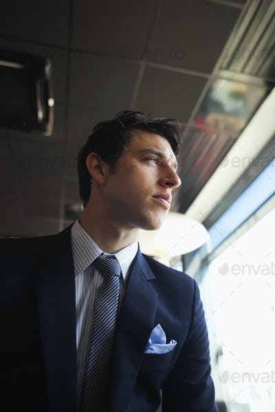 Low angle view of businessman looking through window at coffee shop