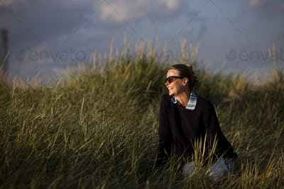 Happy young woman sitting on grass at beach