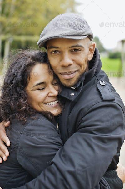 Portrait of happy man hugging woman