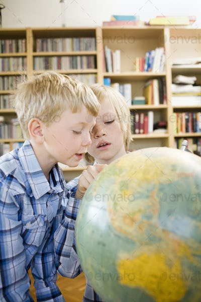 Boy showing brother map on globe at home