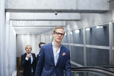 Portrait of businessman with colleagues standing on escalator at railroad station