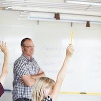 Schoolgirl raising hand while teacher explaining in classroom