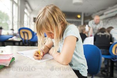 Schoolgirl writing in book at desk in classroom