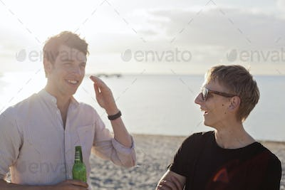Young male friends talking at beach on sunny day