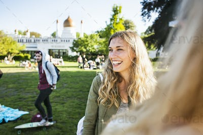 Happy woman looking away while standing with friend at park