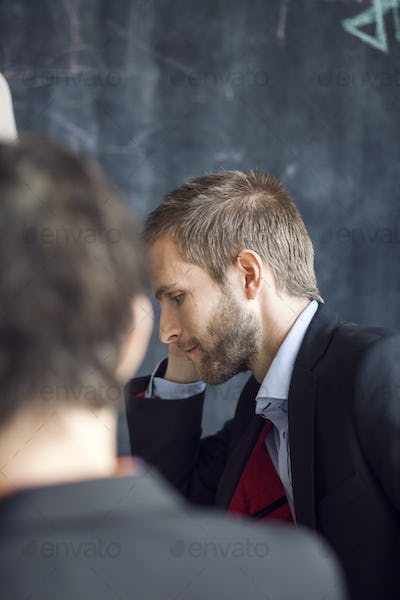 Side view of businessman in meeting with colleague at creative office