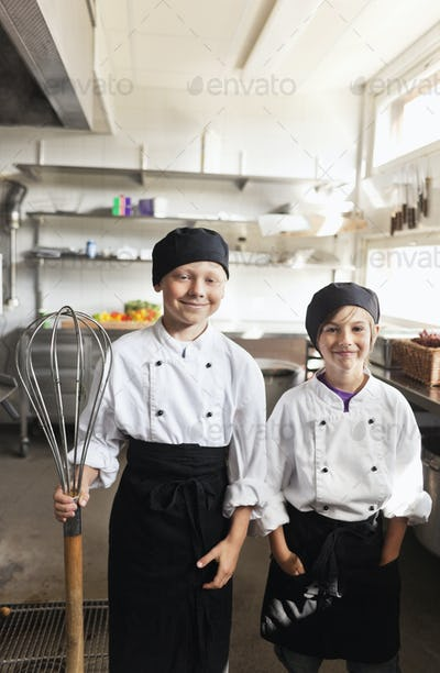 Portrait of happy boys wearing chef's whites while holding wire whisk in restaurant kitchen